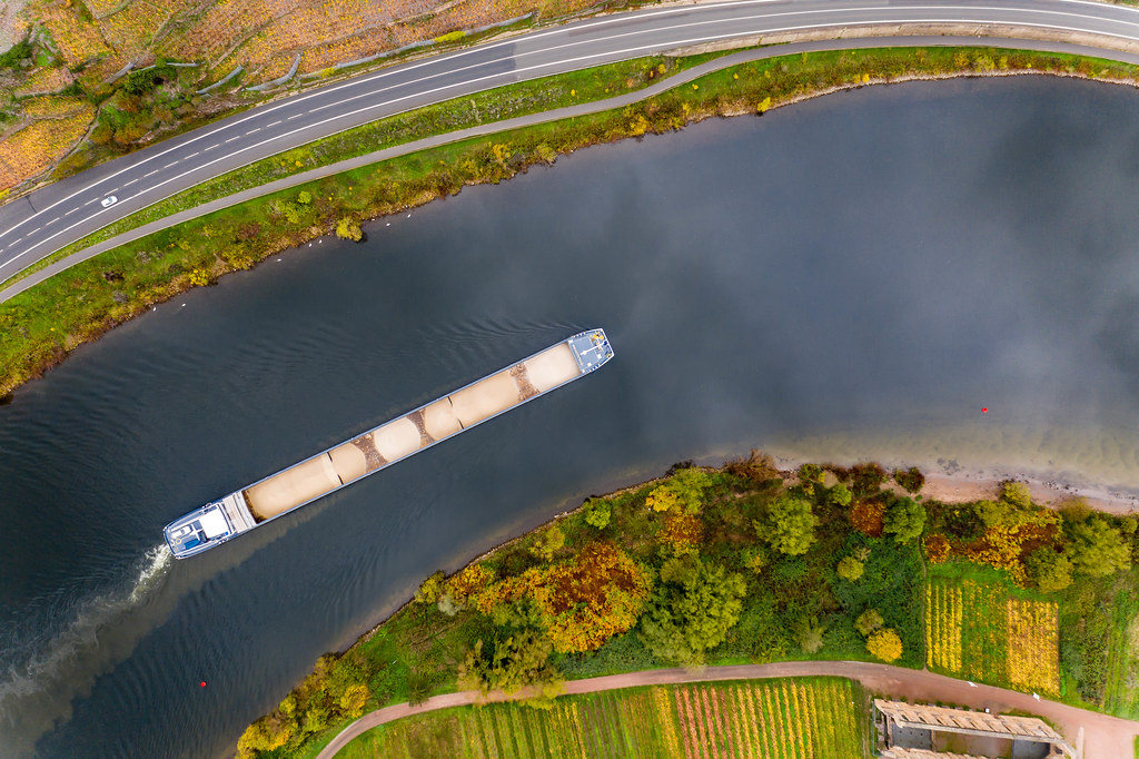 Bird View Drone Photo of Cargo Vessel loaded with Sand on River Moselle along a Highway and Kloster Ruine Stuben in Bremm, Germany