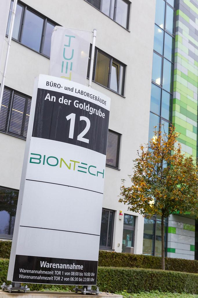 BioNTech Informations-Tafel mit Adresse An der Goldgrube 12 in Mainz und Warenannahme Öffnungszeiten mit BioNTech Gebäude und Flagge im Hintergrund