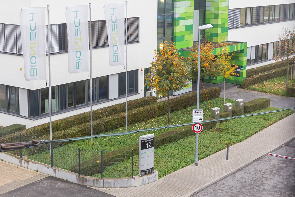 Main Entrance of BioNTech Headquarters with Flag Poles and BioNTech Flags in front of it in Mainz, Germany