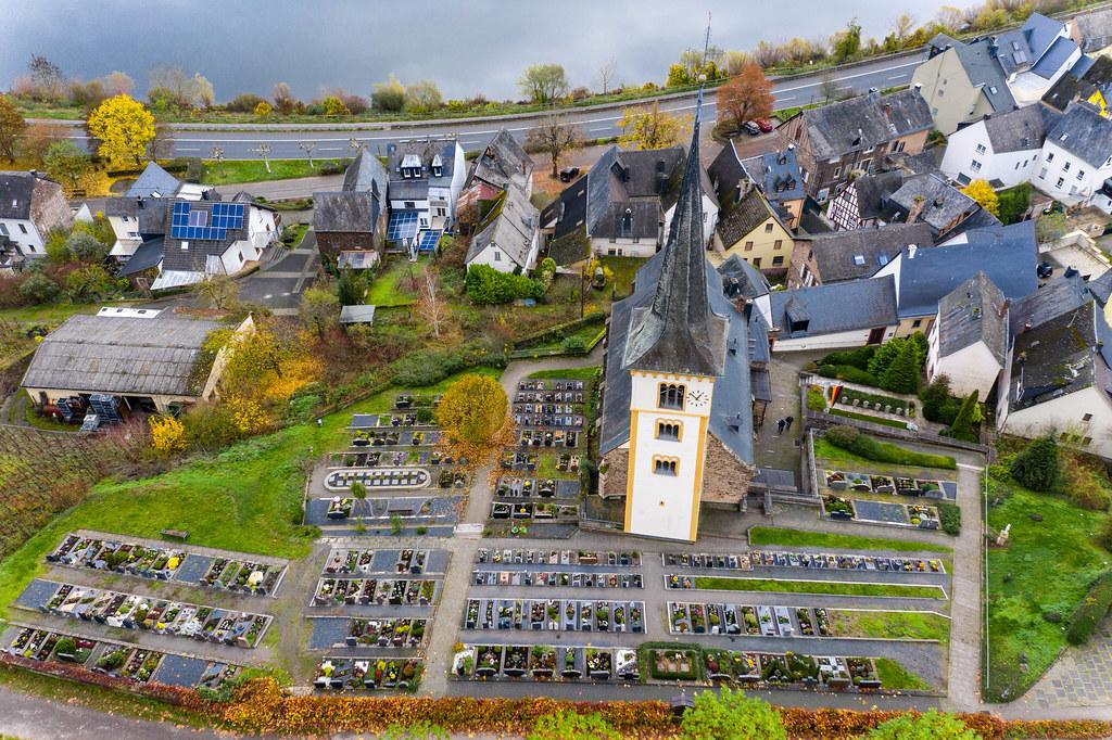 Drohnenaufnahme der St. Laurentius Kirche mit Parkplatz und Häusern an dem Fluss Mosel in Bremm, Deutschland