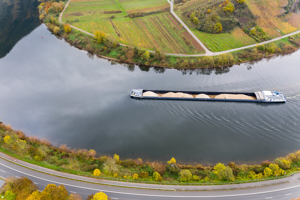 Aerial View of Cargo Vessel transporting Sand on River Moselle along Highway B49 in Bremm, Germany