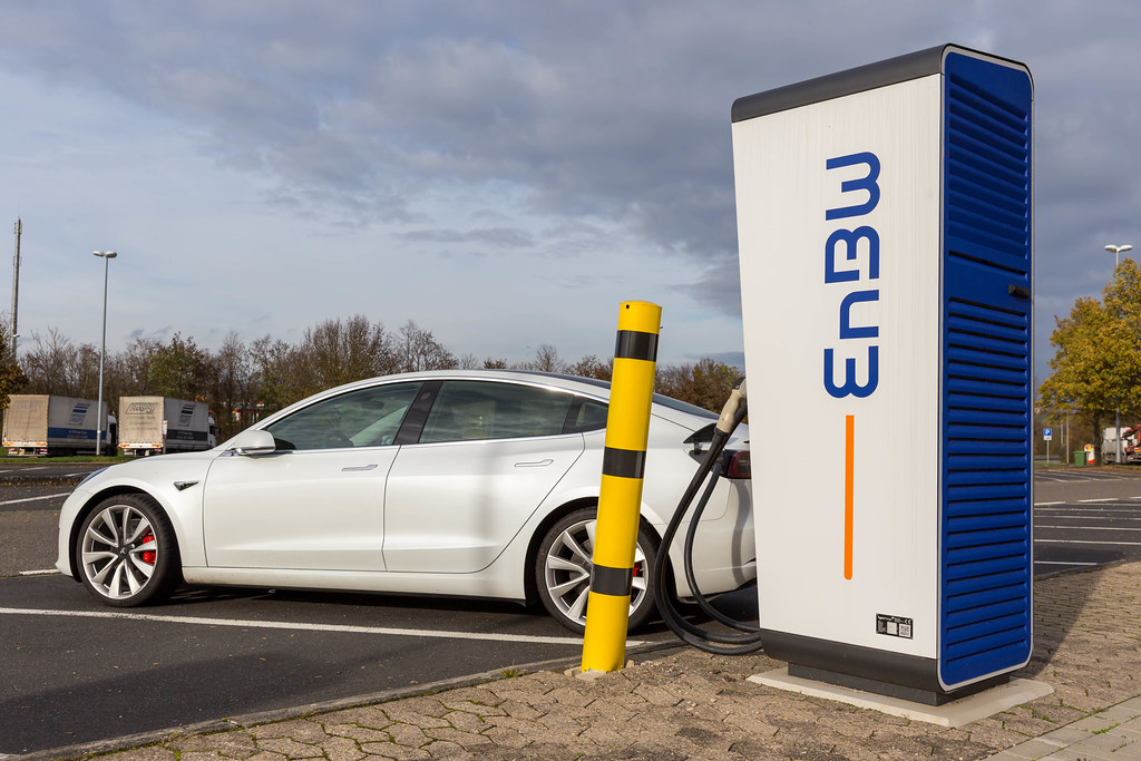 Electric Vehicle Tesla Model 3 is charging on a mobility+ Charging Station of EnBW at a Rest Stop in Germany