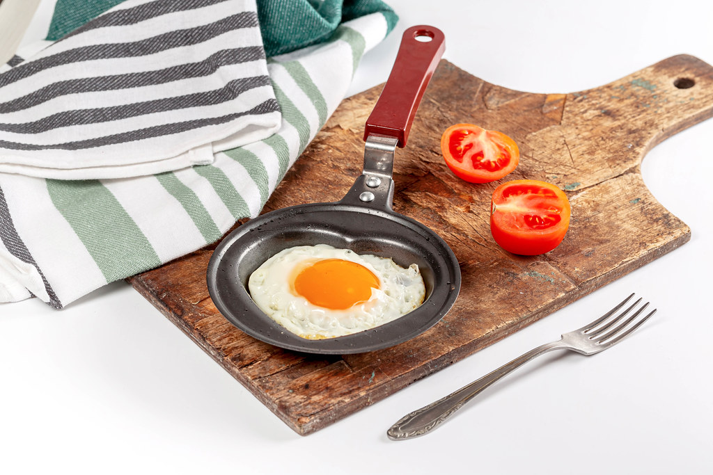 Breakfast background with fried egg in a frying pan with tomato slices