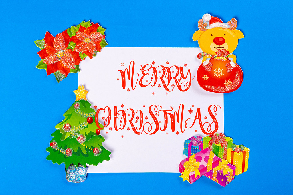 Merry christmas greeting lettering with gifts, christmas tree and deer
