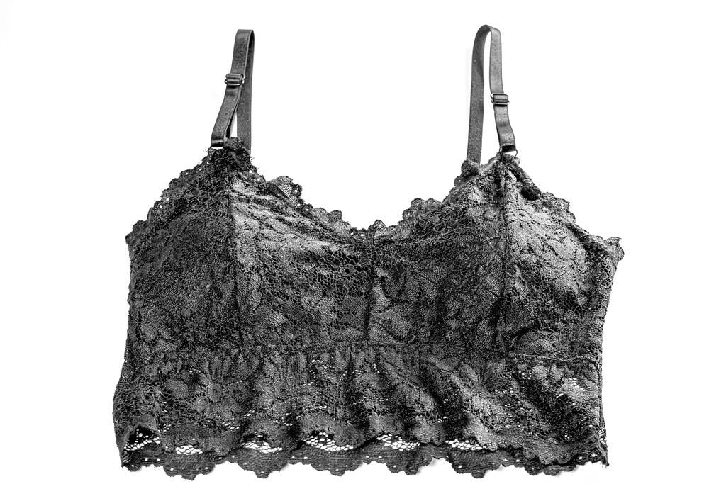 Black lace bra on white, top view