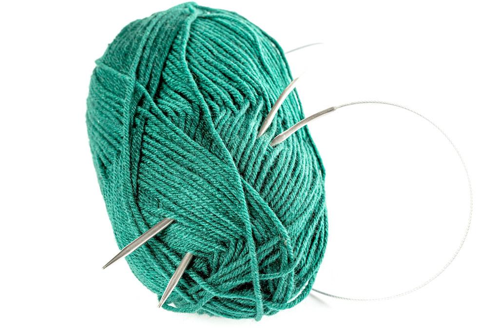 Ball of green knitting wool or yarn, with knitting needles
