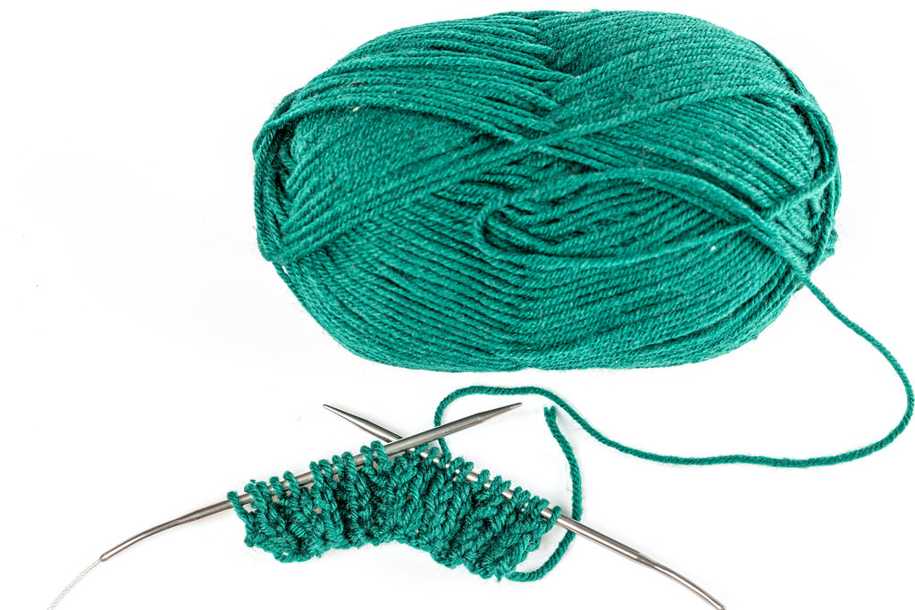 Top view, ball of green yarn with knitting needles