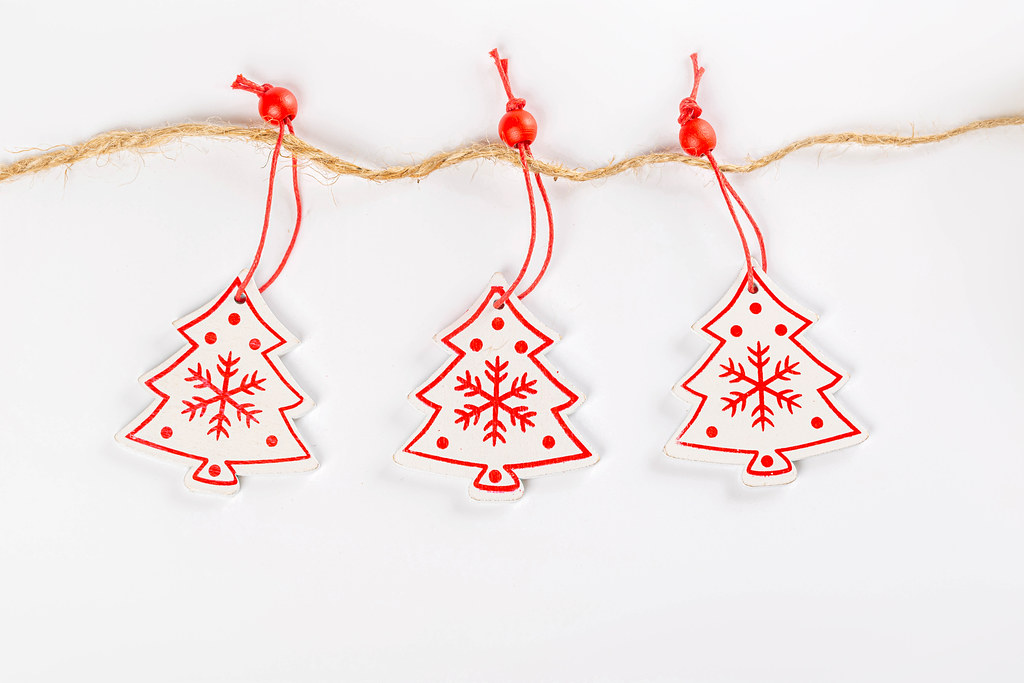 Three wooden Christmas trees toys hang on a rope