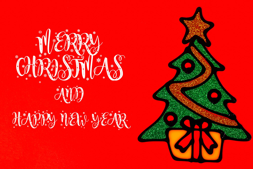 Merry Christmas and happy new year greeting card with Christmas tree on red background