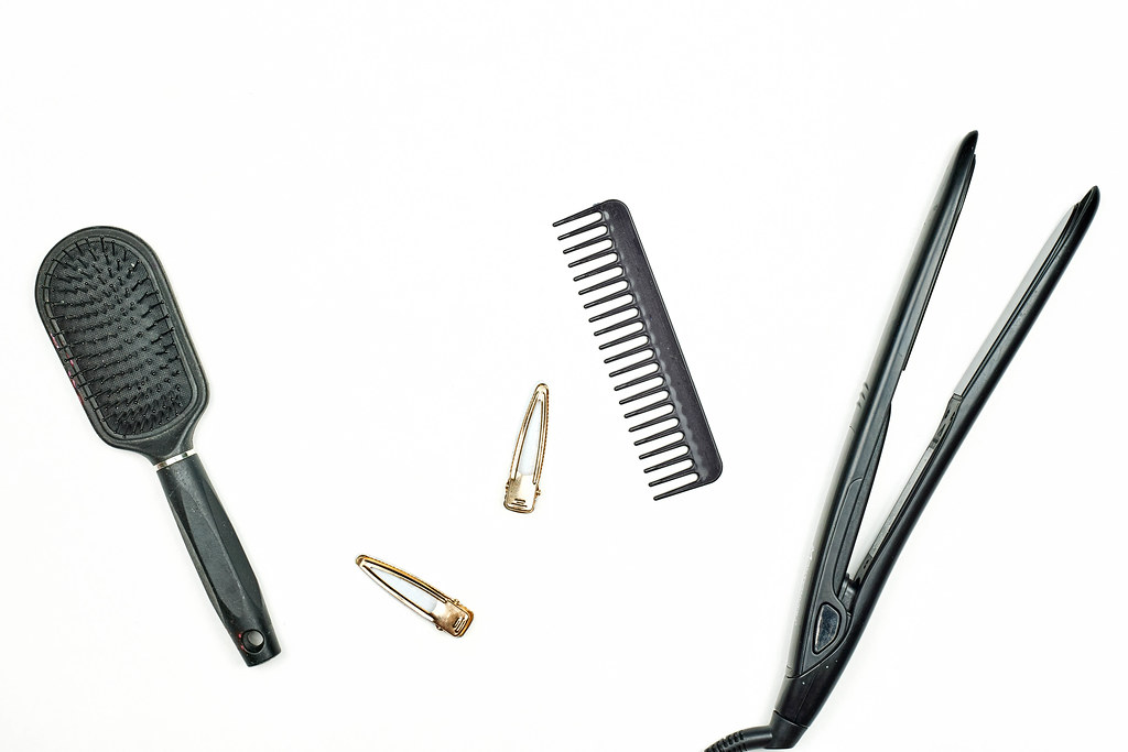 Two comb and electric hair straightener on white