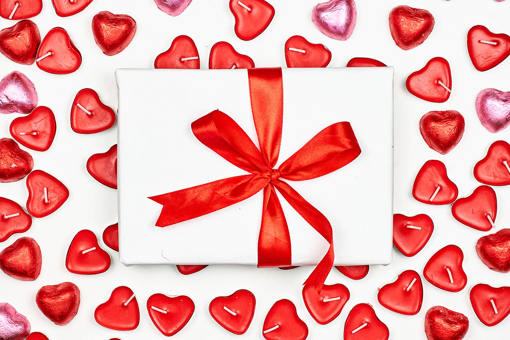 A giftbox over the heart-shaped candles on white