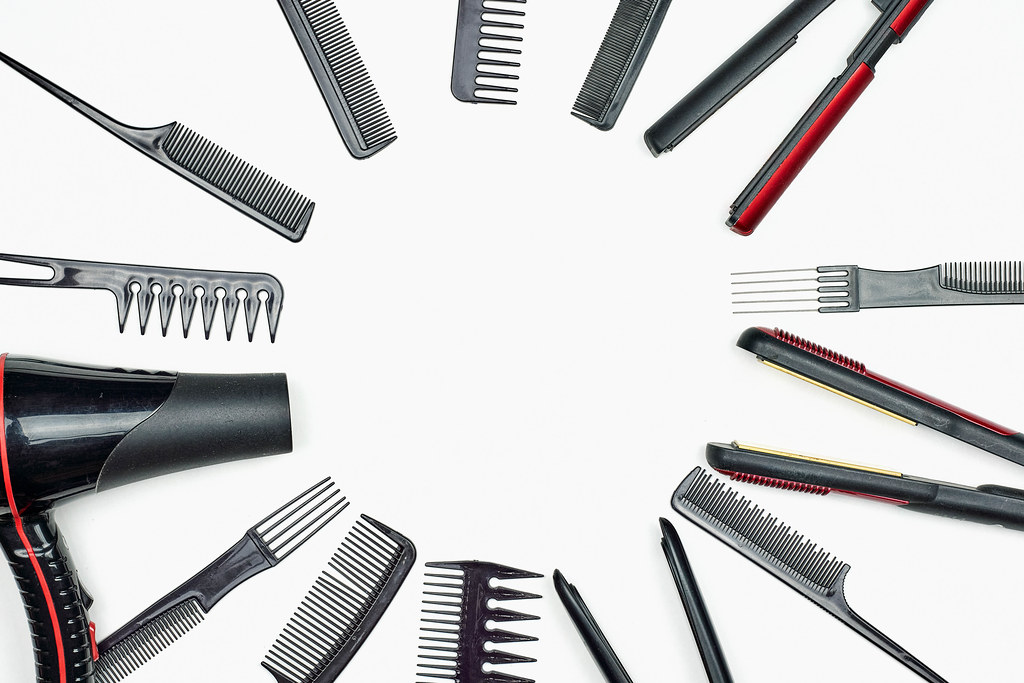 Hairdresser tools on white background with copy space in center