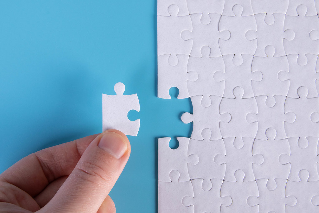 Hand placing the last jigsaw puzzle piece