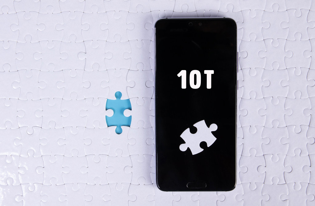 A modern big smartphone with a touch screen lies on a white jigsaw puzzle with 10T text