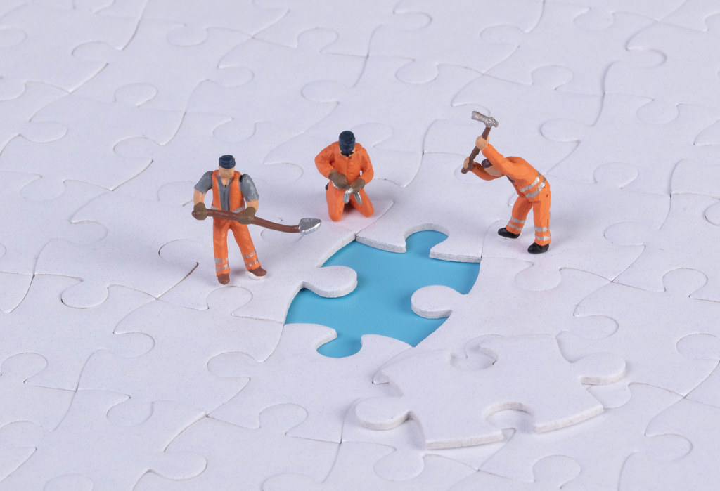Miniature people team trying to complete the last jigsaw puzzle piece
