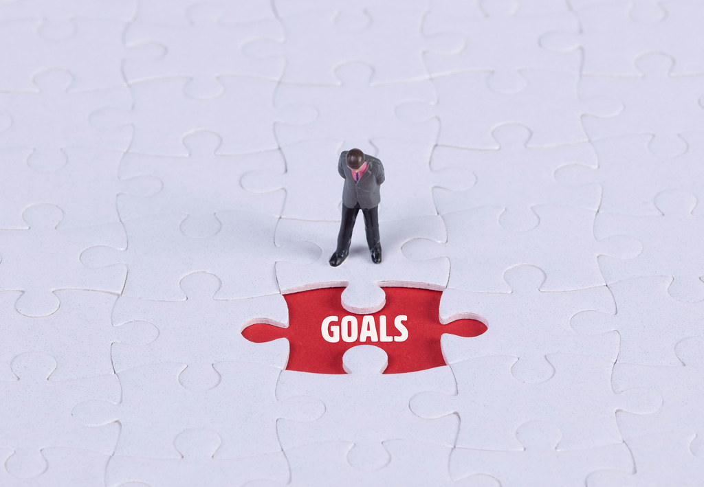 Miniature man looking at a missing puzzle piece with Goals text