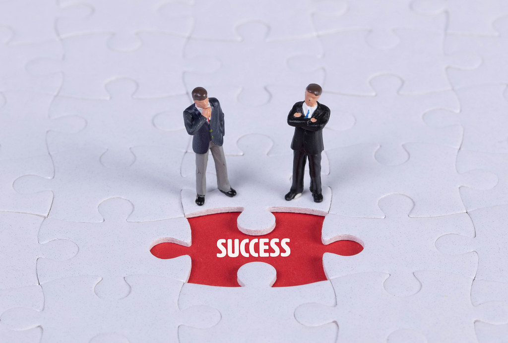 Two miniature man looking at a missing puzzle piece with Success text