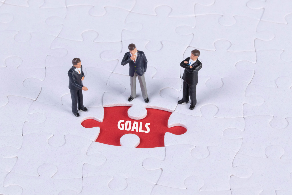 Group of miniature man looking at a missing puzzle piece with Goals text