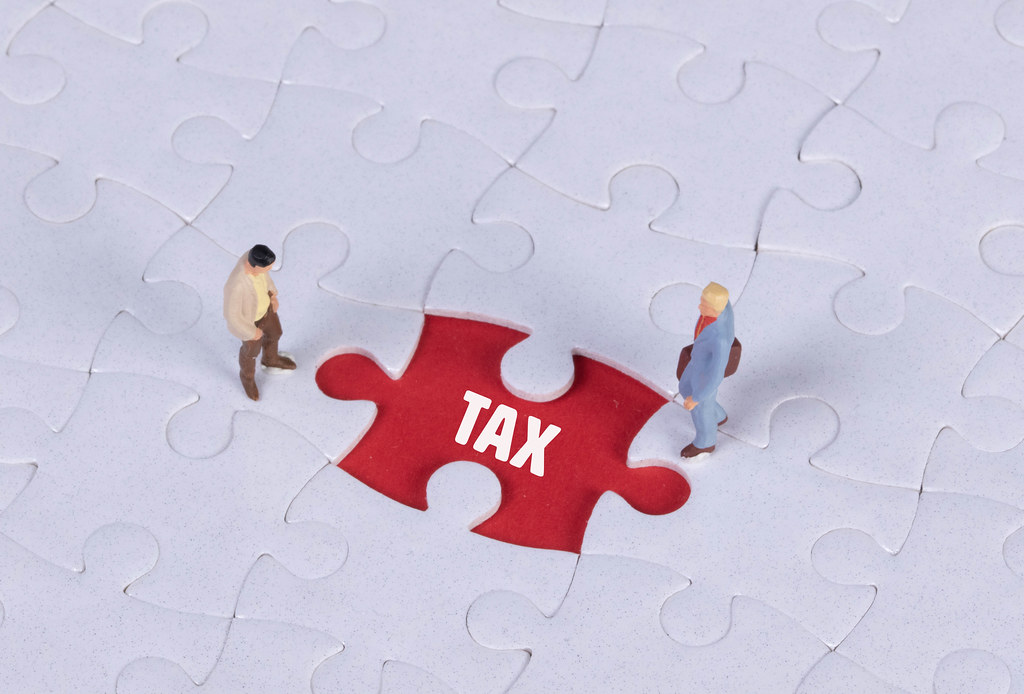 Two miniature man looking at a missing puzzle piece with Tax text