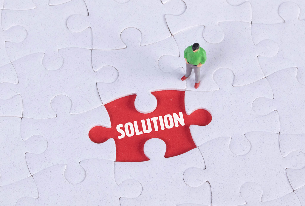 Miniature man looking at a missing puzzle piece with Solution text