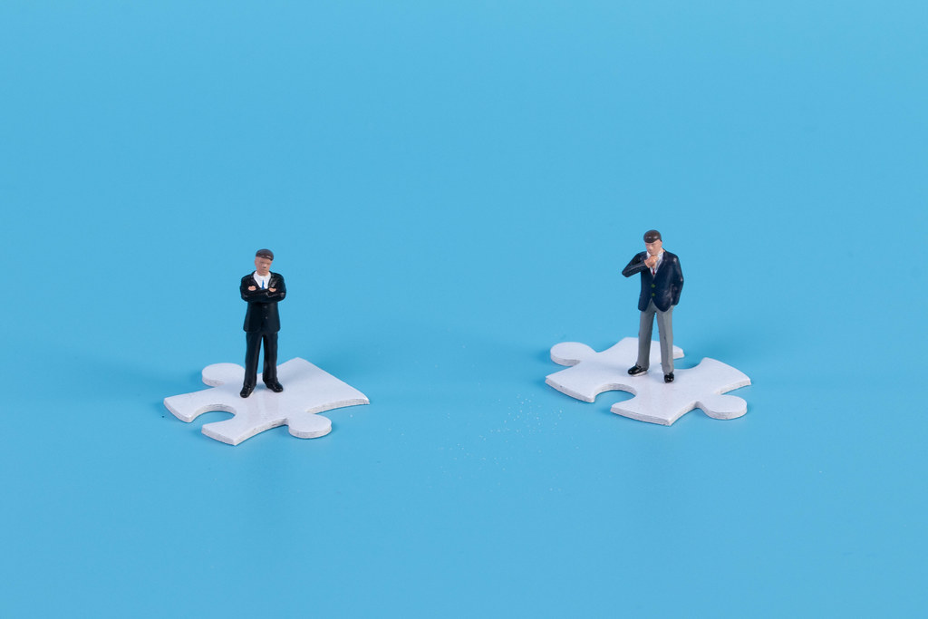 Miniature businessman standing on white jigsaw puzzle piece