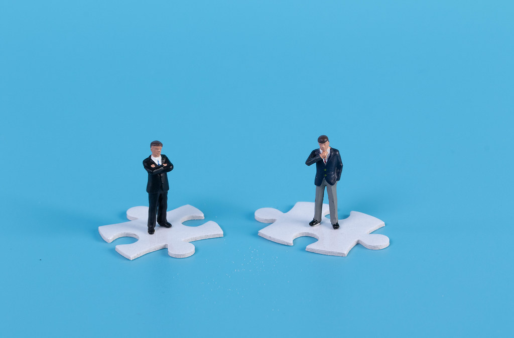 Miniature businessman standing on white jigsaw puzzle piece with blue background