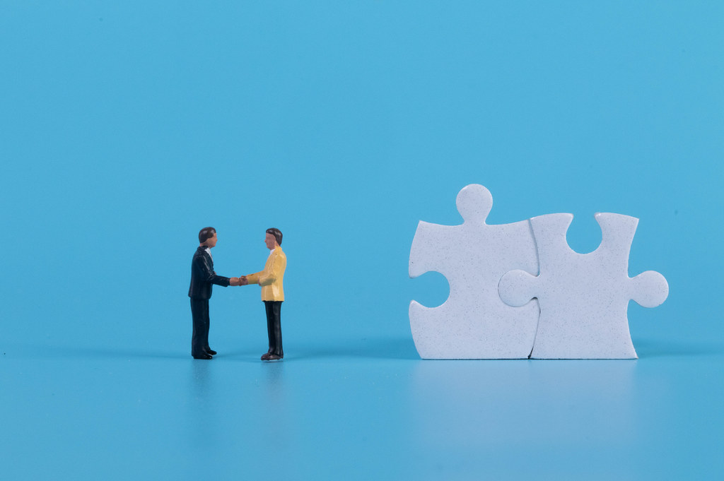Miniature businessman handshaking with white jigsaw puzzle pieces