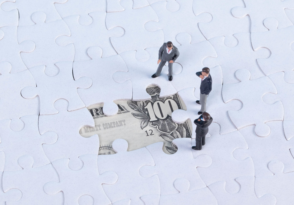Group of businessman with missing jigsaw puzzle pieces over money dollar background