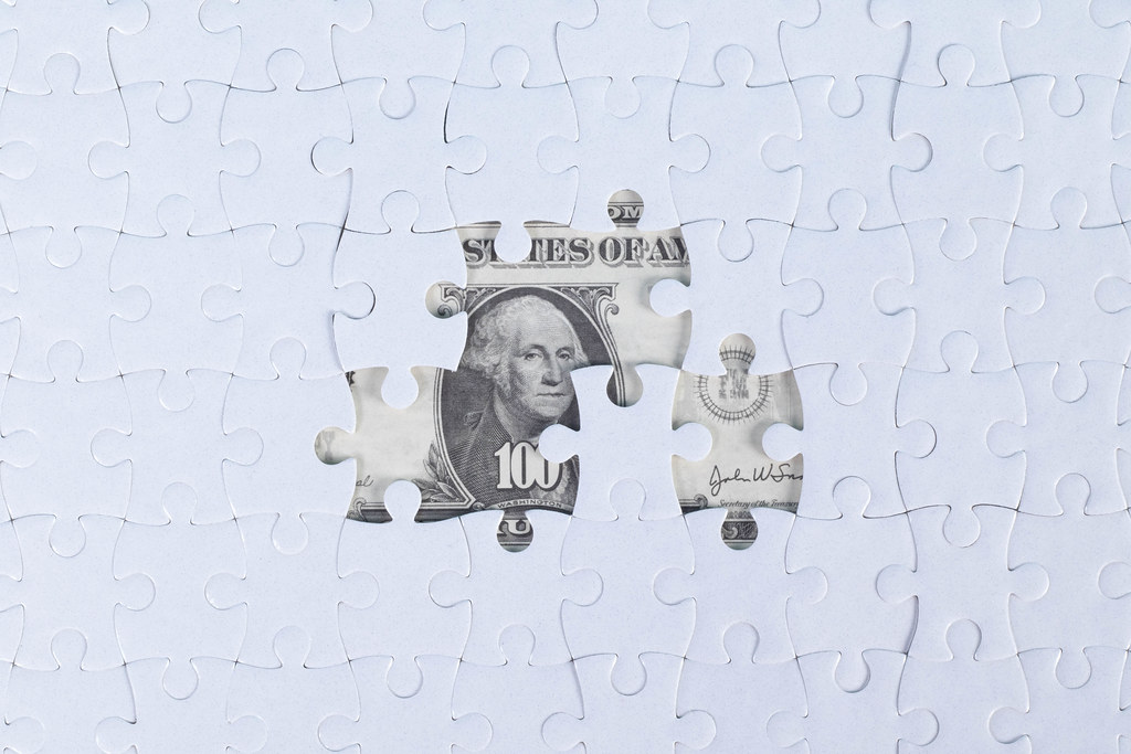 Missing jigsaw puzzle pieces on money dollar background