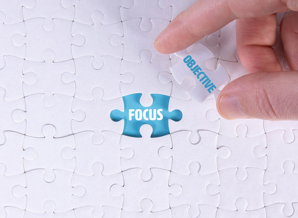 Hand holding piece of jigsaw puzzle with word focus & objective