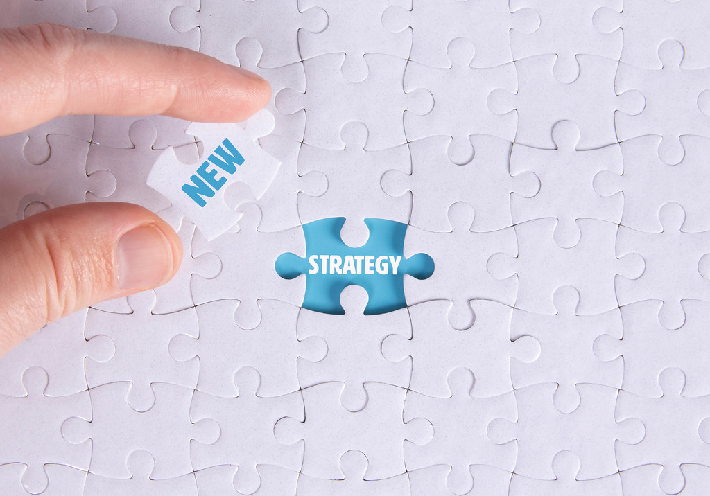 Hand holding piece of jigsaw puzzle with word new & strategy
