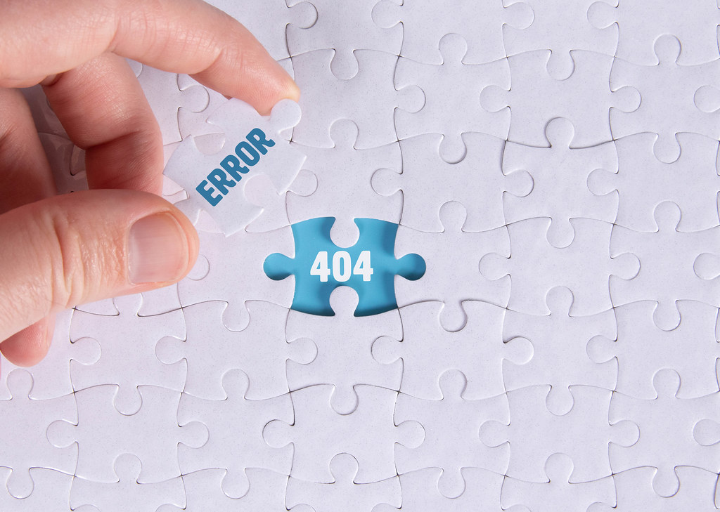 Hand holding piece of jigsaw puzzle with word error & 404