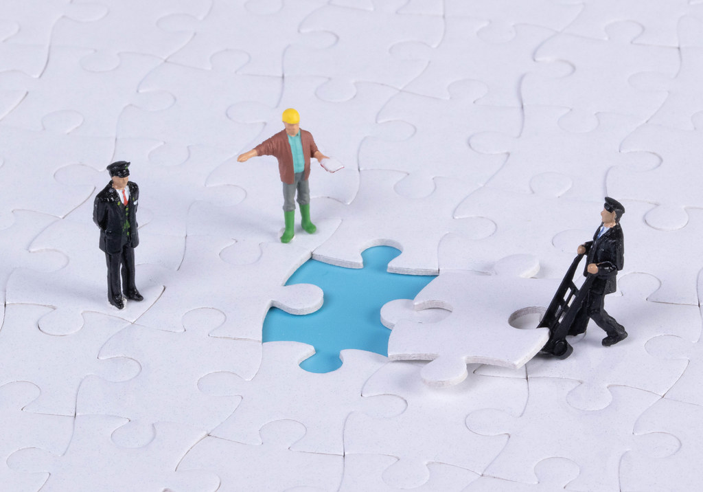 Group of miniature people assembling jigsaw puzzle