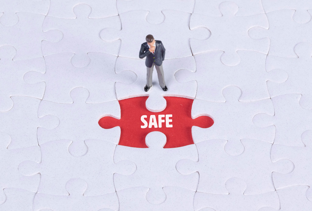 Miniature man looking at a missing puzzle piece with Safe text