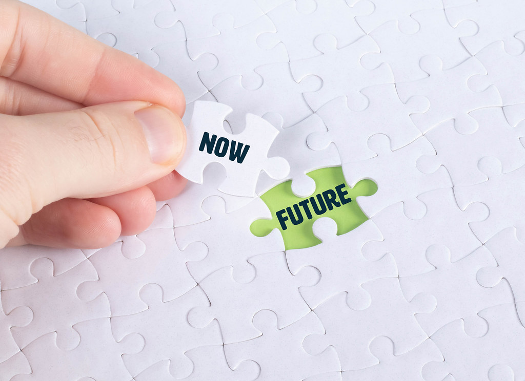 Hand holding piece of jigsaw puzzle with word now & future