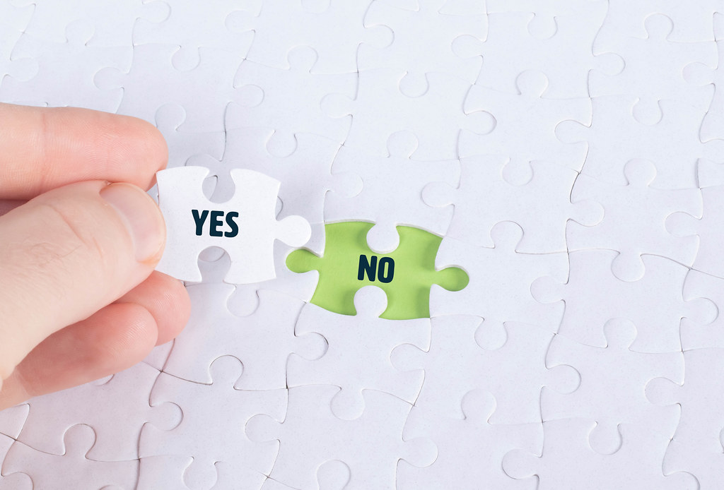 Hand holding piece of jigsaw puzzle with word yes & no
