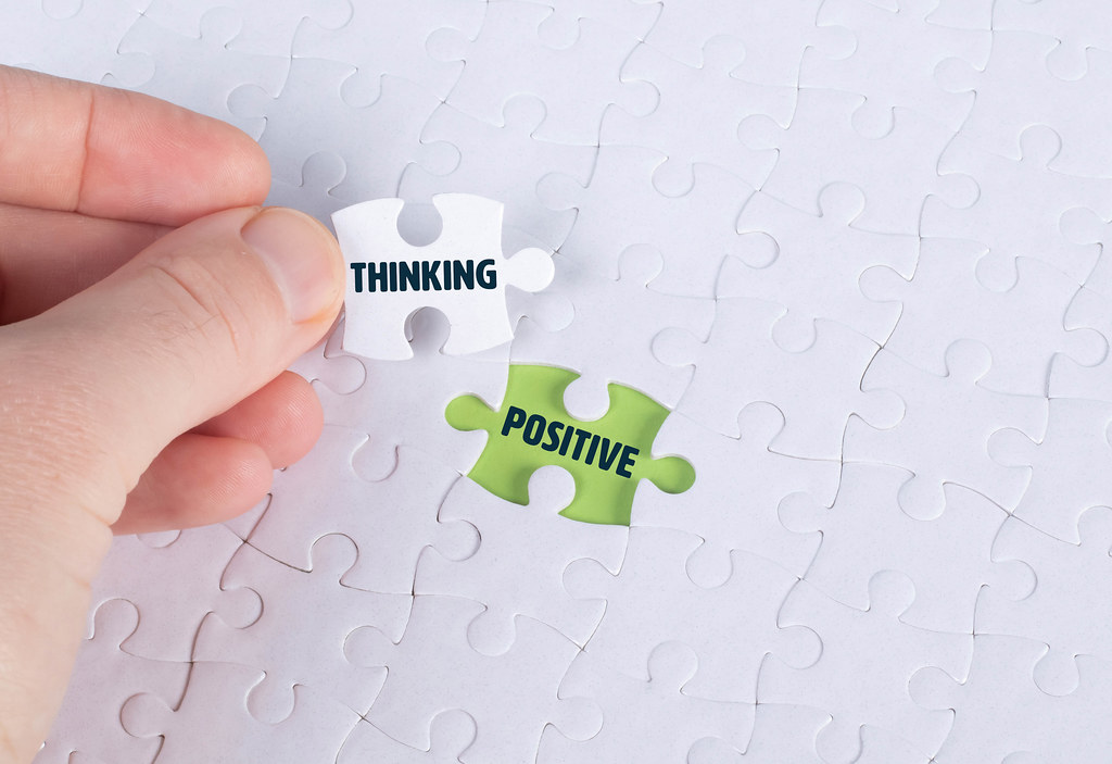 Hand holding piece of jigsaw puzzle with word thinking & positive