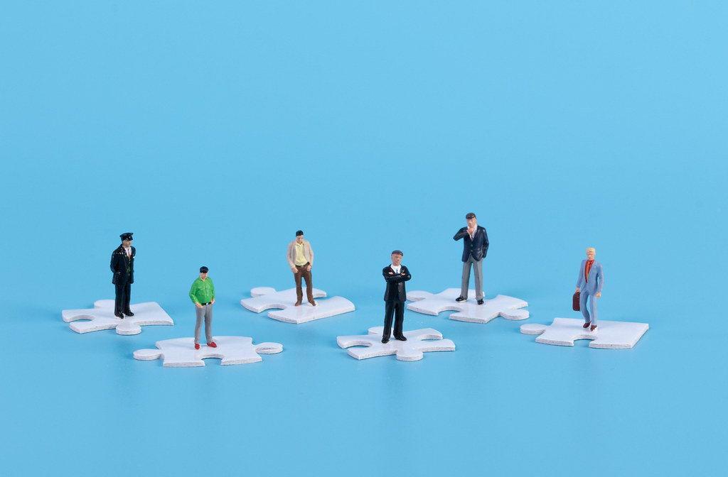 Miniature people standing on white jigsaw puzzle pieces