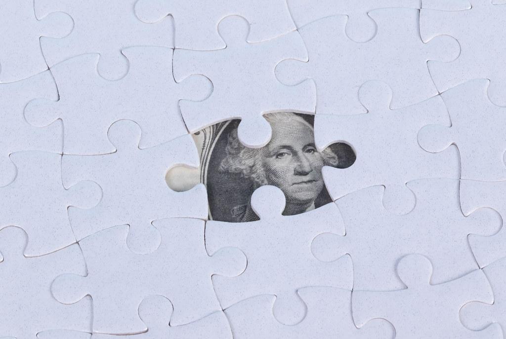 Missing jigsaw puzzle piece on 100 Dollar money background