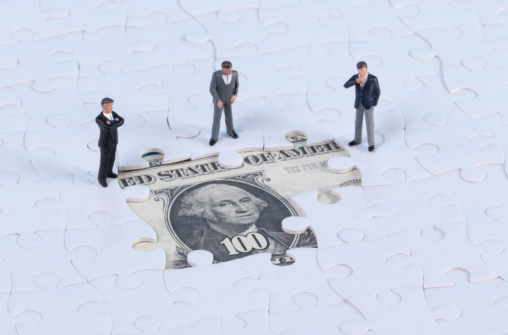 Group of miniature businessman with missing jigsaw puzzle pieces on money dollar background