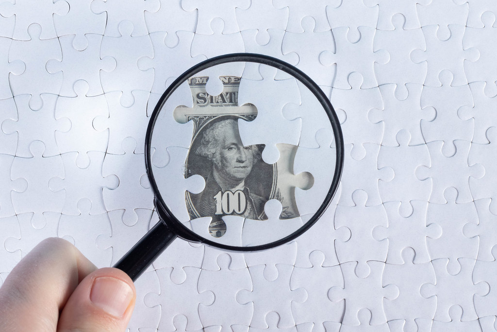 Magnifier and white puzzle on hundred dollars banknotes