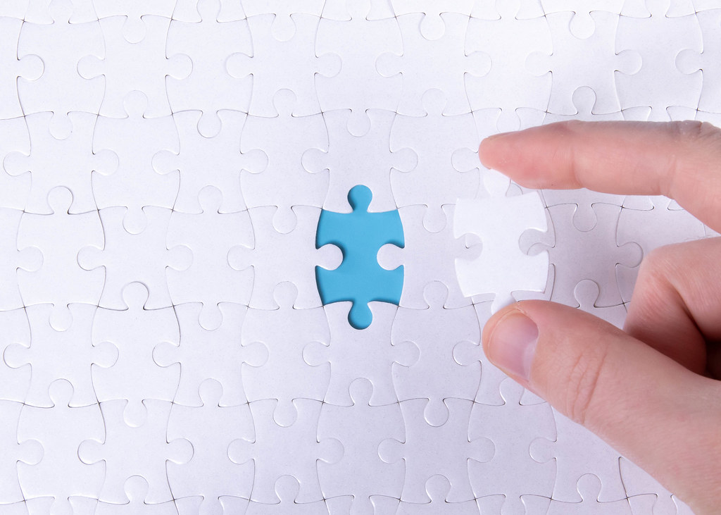 The texture of a white jigsaw puzzle in the assembled state with one missing element that the male hand puts in