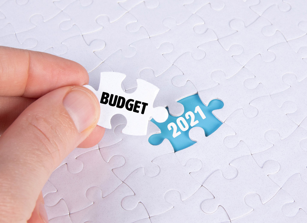 Hand holding piece of jigsaw puzzle with text budget & 2021