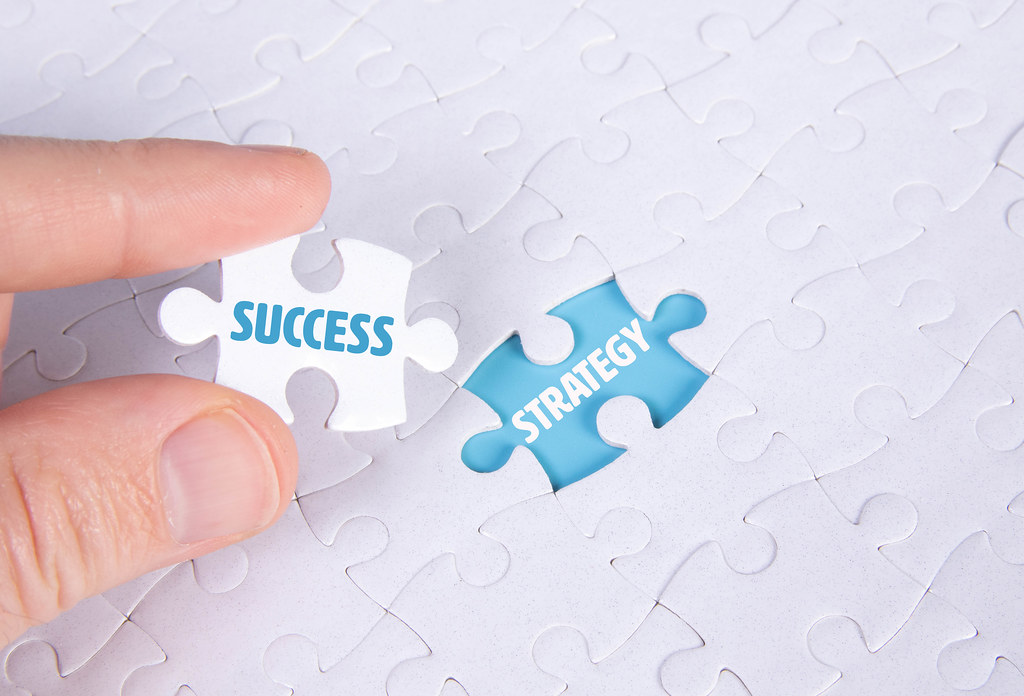 Hand holding piece of jigsaw puzzle with word success & strategy