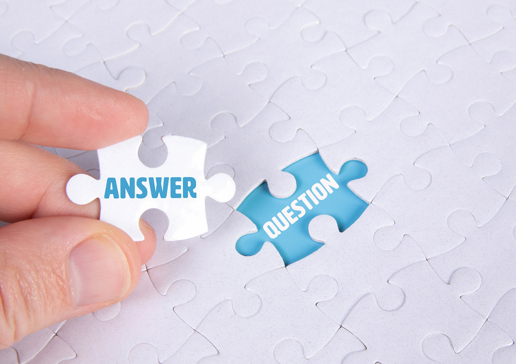 Hand holding piece of jigsaw puzzle with word answer & question