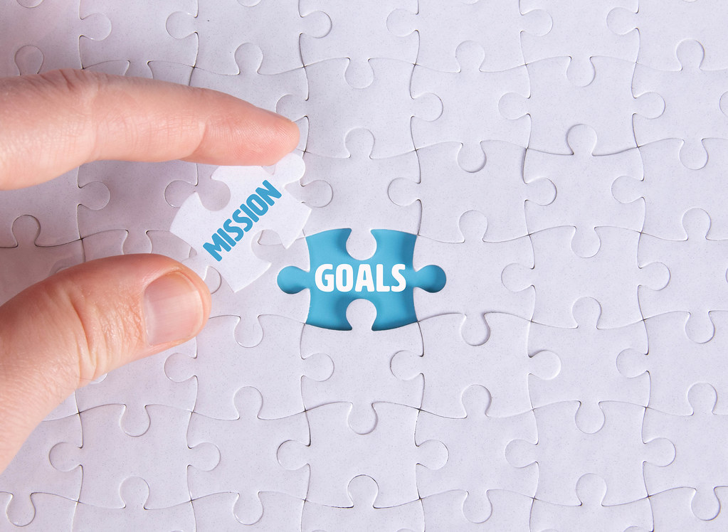 Hand holding piece of jigsaw puzzle with word mission & goals