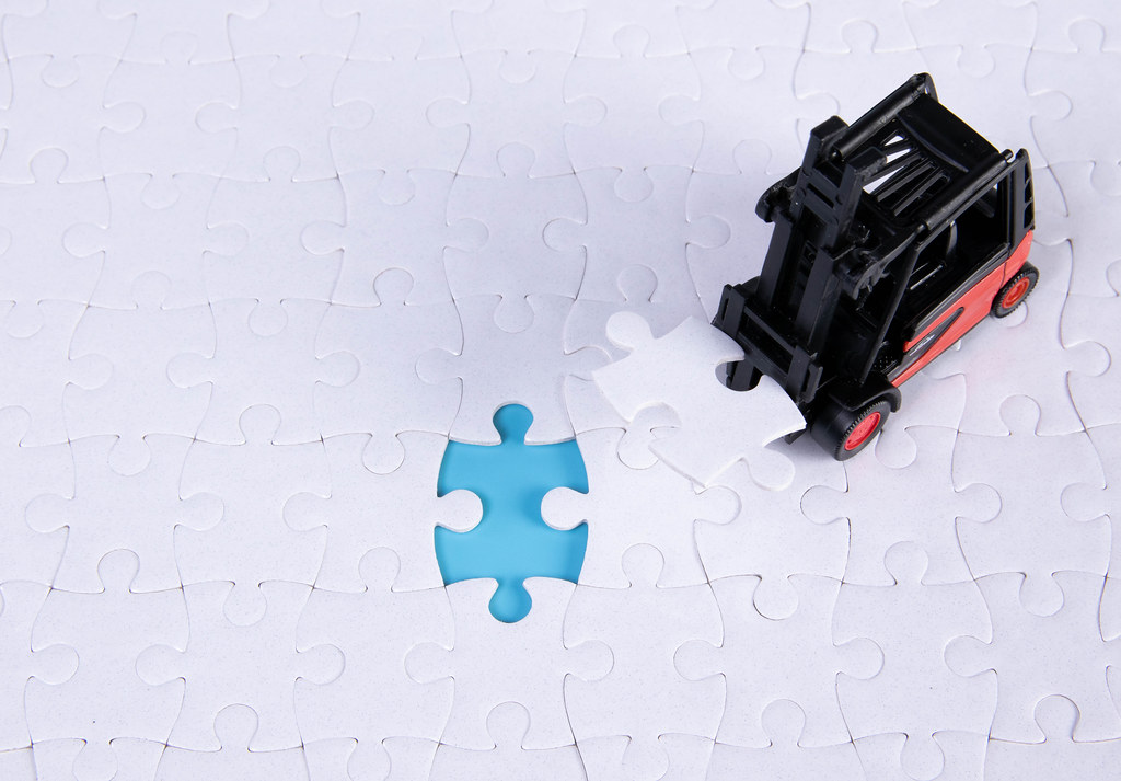 A forklift truck picks up the missing puzzle piece