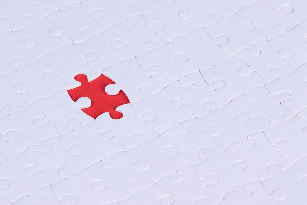 Top view of jigsaw puzzle with one piece left on red background