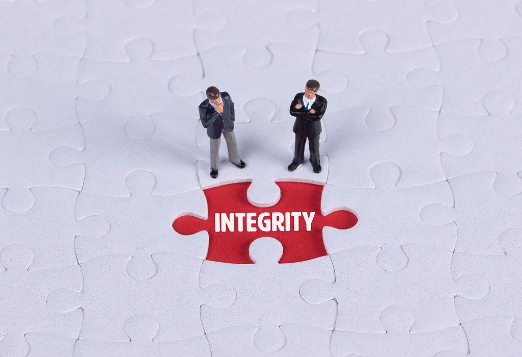 Two miniature man looking at a missing puzzle piece with Integrity text
