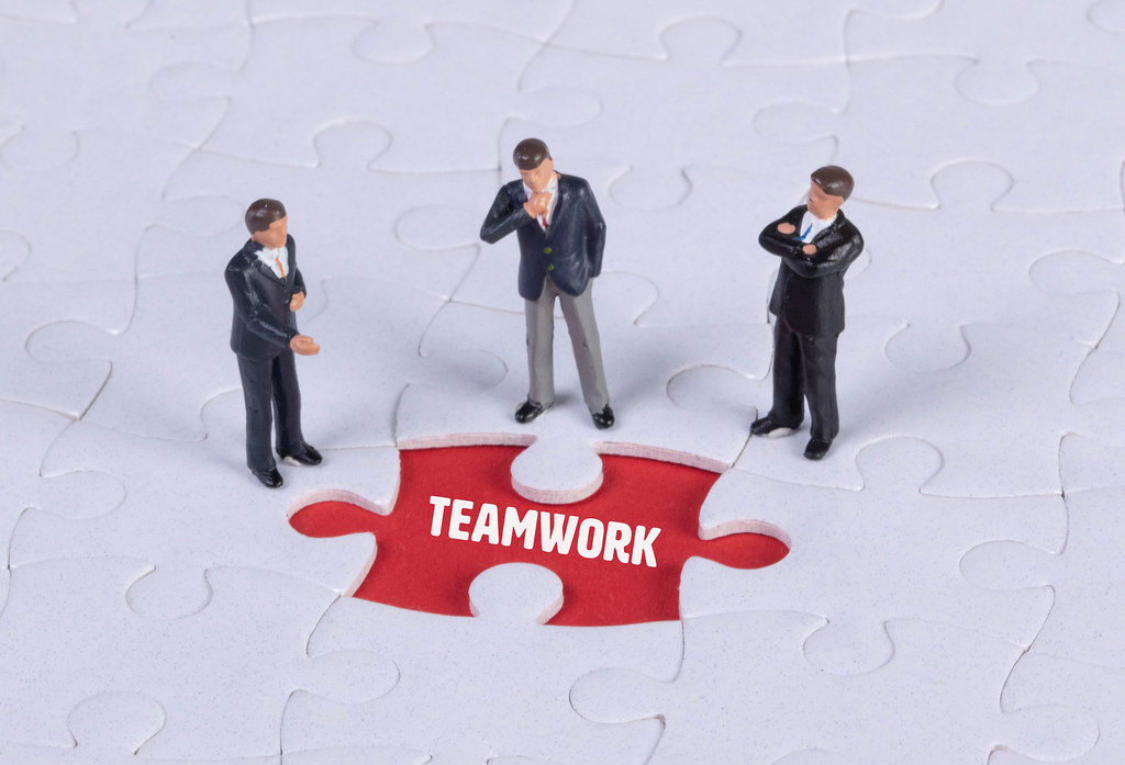 Group of miniature man looking at a missing puzzle piece with Teamwork text